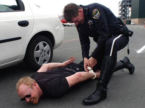 Adam Savage being handcuffed