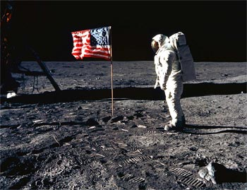 Buzz Aldrin in front of flag Apollo 11